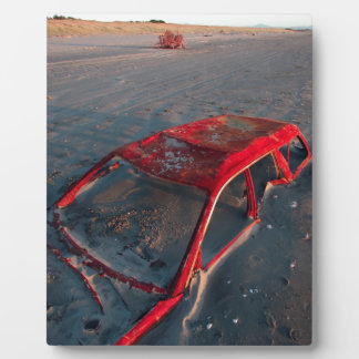 Rusty car wreck buried in sand on beach plaque