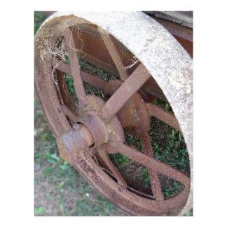 Rusty iron wheel of old cart letterhead