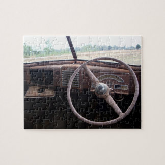 Rusty old car wreck interior, with steering wheel jigsaw puzzle
