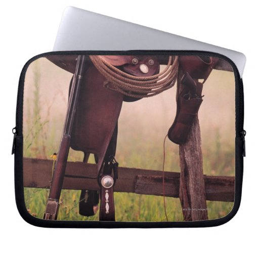 Saddle and lasso on fence computer sleeves