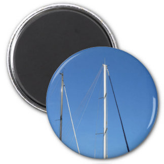 Sailboat masts in the marina against a blue sky magnet