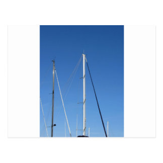 Sailboat masts in the marina against a blue sky postcard