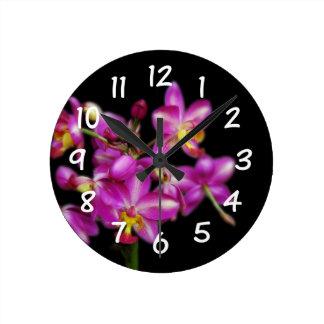 Sala de estar - orquídeas púrpuras en fondo negro reloj redondo mediano