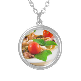Salad of blanched pieces of seafood on a plate silver plated necklace