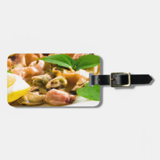 Salad of blanched seafood on a white plate luggage tag