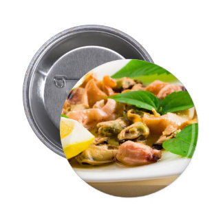Salad of blanched seafood on a white plate pinback button