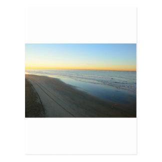 Salida del sol de Huntington Beach en la playa Postal