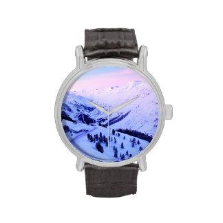 Salida del sol de la nieve de la montaña reloj de mano