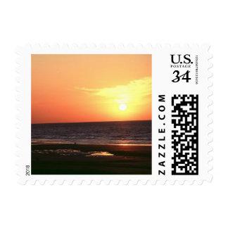 Salida del sol de la playa de la postal sellos