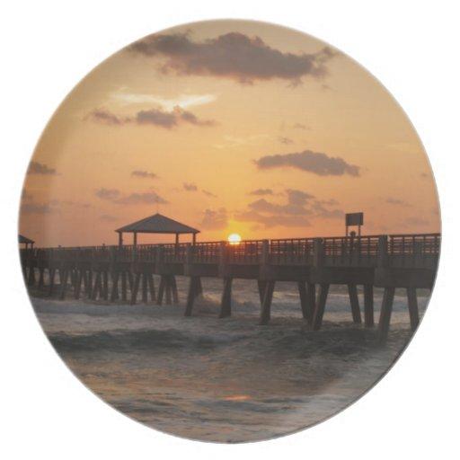 Salida del sol en el embarcadero de la playa de Ju Plato De Comida
