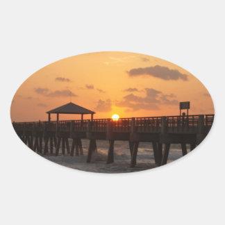 Salida del sol en el embarcadero de la playa de pegatinas de oval personalizadas