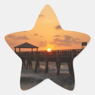 Salida del sol en el embarcadero de la playa de calcomanía forma de estrellae