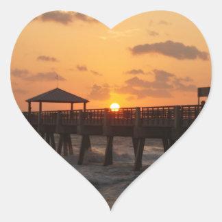 Salida del sol en el embarcadero de la playa de calcomanía de corazón
