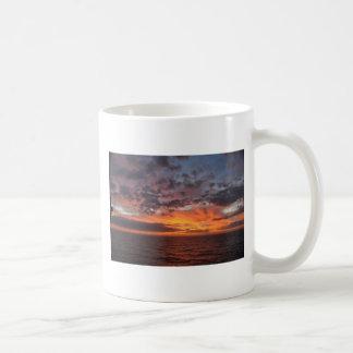 Salida del sol en el golfo tazas de café