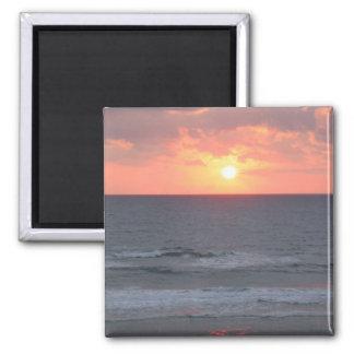 Salida del sol en el imán de la playa