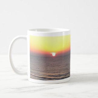 Salida del sol en la playa tazas de café