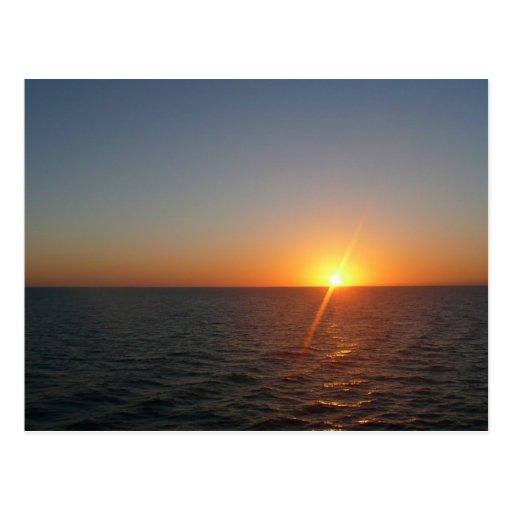 Salida del sol en la postal del mar