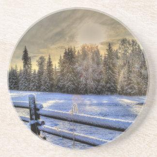 Salida del sol en un pasto del invierno en nieve posavasos diseño