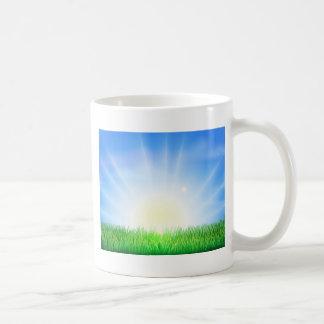 Salida del sol sobre el campo verde de la hierba tazas