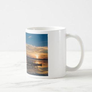 Salida del sol sobre el embarcadero taza de café