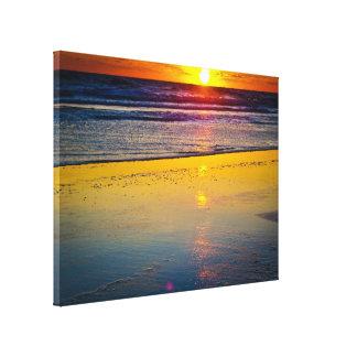Salida del sol sobre el océano y reflejada en la impresión en lona estirada