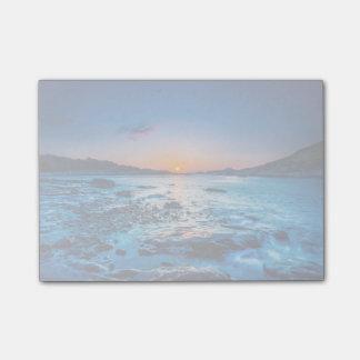 Salida del sol sobre horizonte en la costa en el notas post-it®