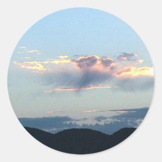 Salida del sol sobre la montaña del remache en el etiqueta redonda