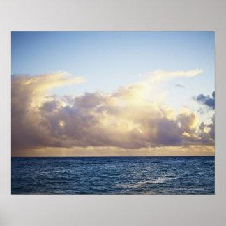 Salida del sol y nubes sobre el océano póster