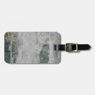 Salpica del agua de la fuente en un día soleado etiqueta de equipaje