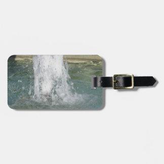 Salpica del agua de la fuente en un día soleado etiquetas maleta