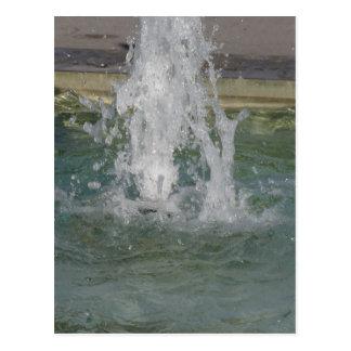 Salpica del agua de la fuente en un día soleado postal