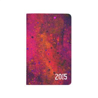 Salpicadura azul rosada roja de la pintura del cuadernos grapados