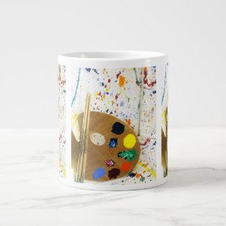 Salpicadura de la pintura de los artistas y taza grande