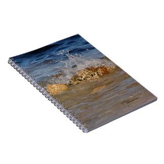 Salpicar la onda contra el cuaderno de la roca