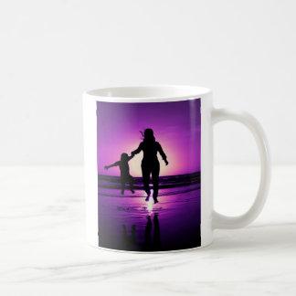 Salto de la playa del niño de la madre y del hijo taza de café