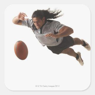Salto masculino del jugador del rugbi para la bola pegatina cuadrada
