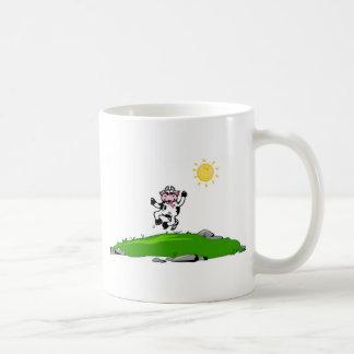 Salto para la vaca de la alegría en hierba taza de café