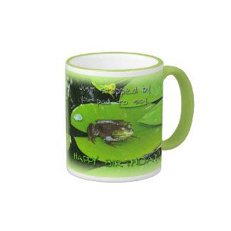 Saludo del feliz cumpleaños - rana mugidora en el taza de dos colores