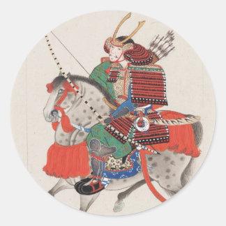 Samurai que lleva a caballo la armadura y el casco pegatina redonda