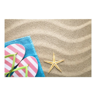 Sand Background With Towel Flip Flops And Starfish Photo