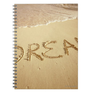 Sand writing 'Dream' with incoming surf at top Notebook