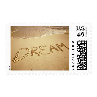 Sand writing 'Dream' with incoming surf at top Postage
