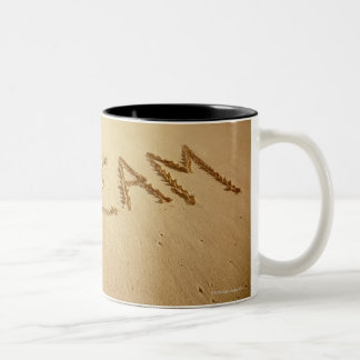Sand writing 'Dream' with incoming surf at top Two-Tone Coffee Mug