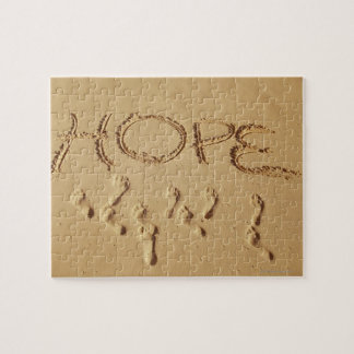 Sand writing ' Hope' on the beach with the Jigsaw Puzzle