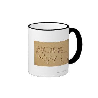 Sand writing Hope on the beach with the Mug