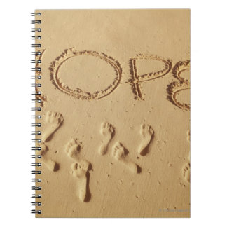 Sand writing Hope on the beach with the Spiral Notebook
