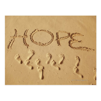 Sand writing ' Hope' on the beach with the Postcard