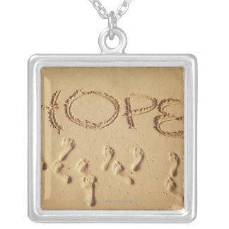 Sand writing ' Hope' on the beach with the Silver Plated Necklace