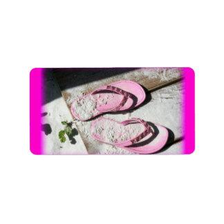 Sandalias arenosas rosadas del flip-flop en la etiquetas de dirección