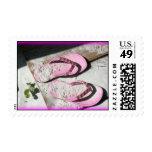 Sandalias arenosas rosadas del flip-flop en la pla
